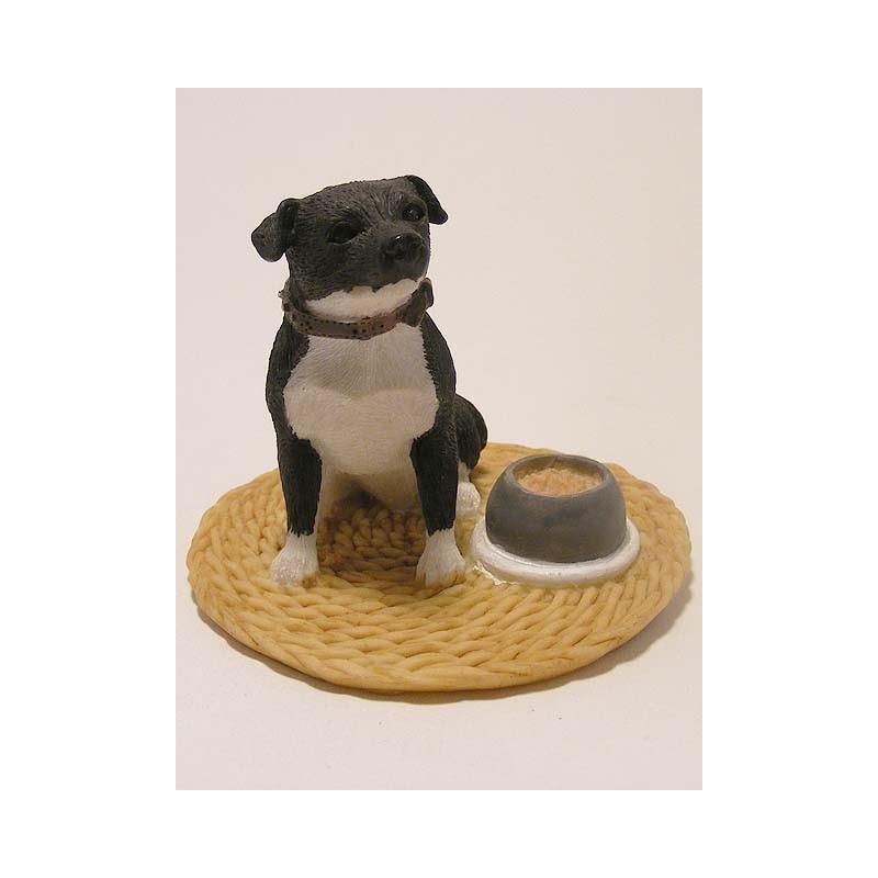 Staffordshire Bull Terrier hond naast zijn etensbak op een vloerkleed