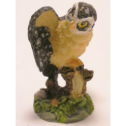 Owl with open wings standing on a branch of synthetic resin