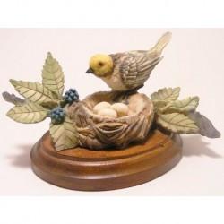 Vogel staand op een nest met eieren op een houten plateau